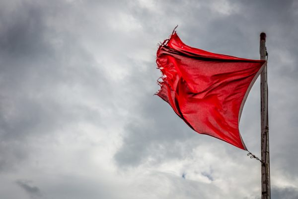 A wind torn red warning flag indicating danger on an English beach.