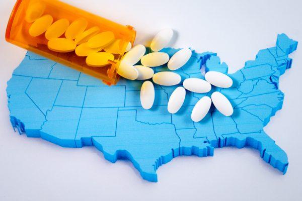 White pharmaceutical pills spilling from prescription bottle over American map