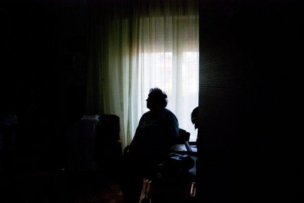 Senior Woman Alone in Dark Room.