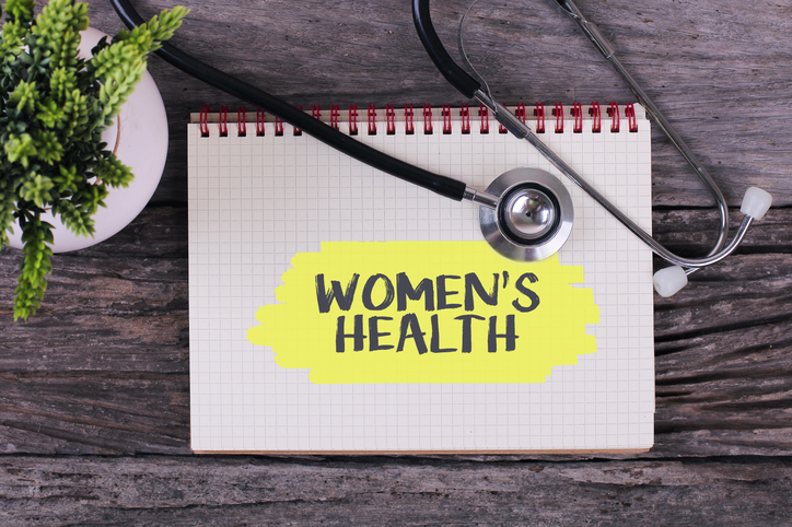 Women's Health word on notebook,stethoscope and green plant