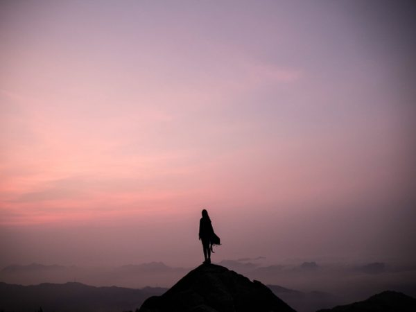 Pioneer Silhouette Woman Standing On Top Of Mountain Against Sky