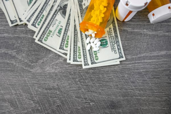 Money pile and medicine pills representing medical expenses