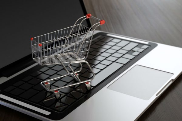 Computer generated image of shopping cart on laptop. E-commerce concept.