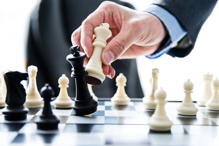 Businessman hand moving the king in a chess game.
