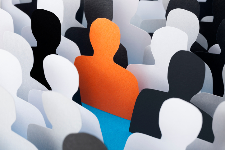 Paper made silhouettes with one of them of orange color to stand out from the rest